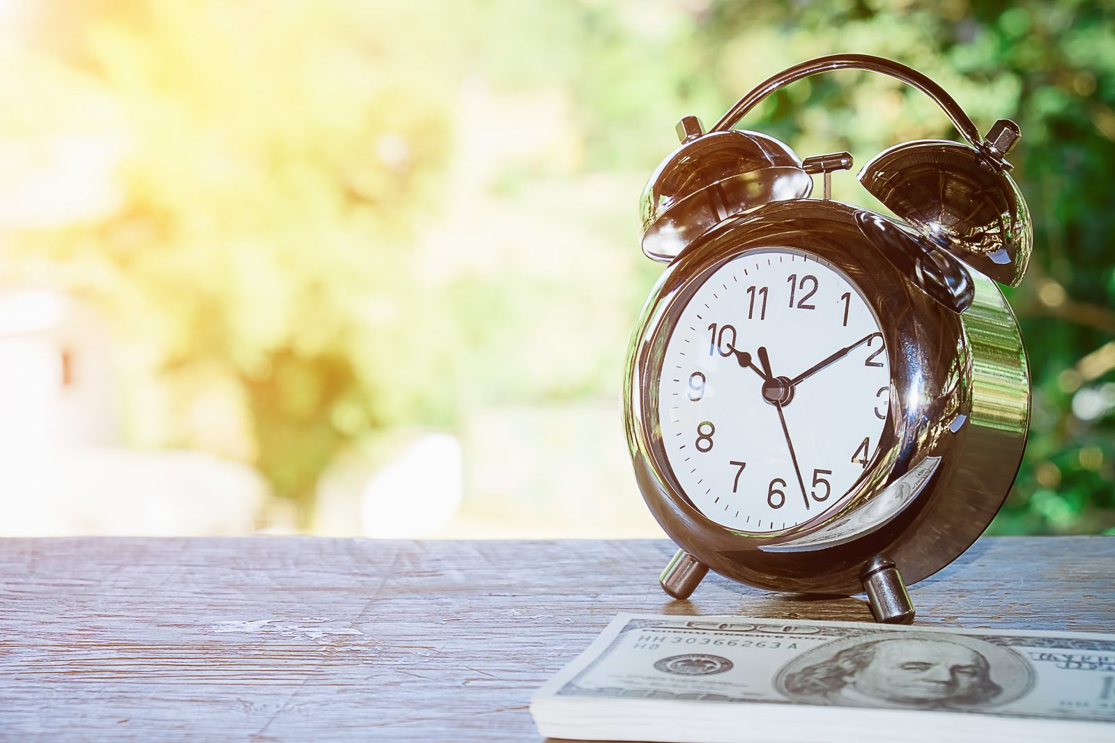 Close up of time and money with green bokeh background ,Business